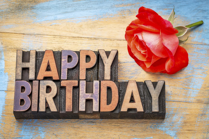 Happy Birthday in wood type. Happy Birthday greeting card - text in vintage letterpress wood type stained by color inks with a red rose stock photo