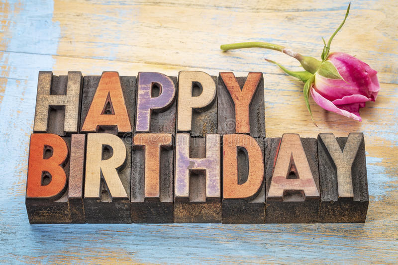 Happy Birthday in wood type. Happy Birthday greeting card - word abstract in vintage letterpress wood type stained by color inks with a pink rose royalty free stock photos