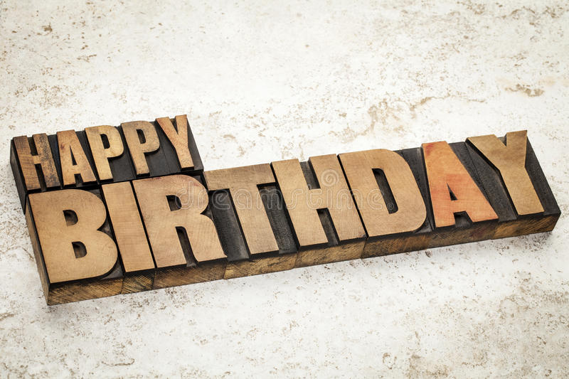 Happy birthday in wood type. Happy birthday text in vintage letterpress wood type on a ceramic tile background stock photography