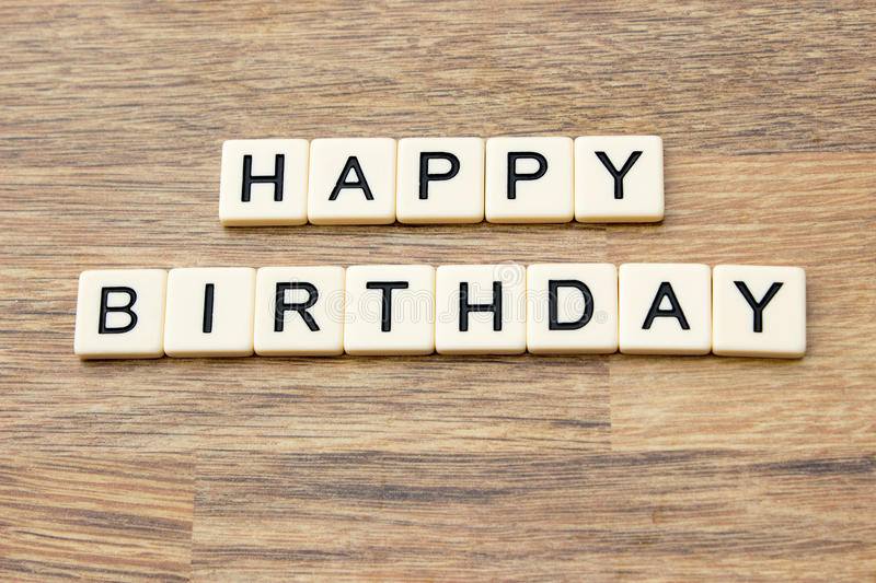 Happy Birthday. The word happy birthday written in tiles on a wooden surface royalty free stock photos
