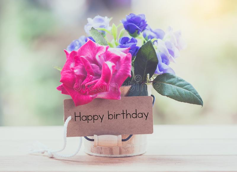 Happy birthday. Writing happy birthday on card with rose on table stock image