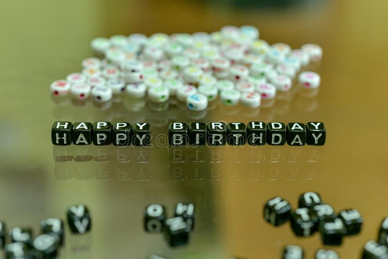 HAPPY BIRTHDAY  written with Acrylic Black cube with white Alphabet Beads on the Glass Background.  royalty free stock photo