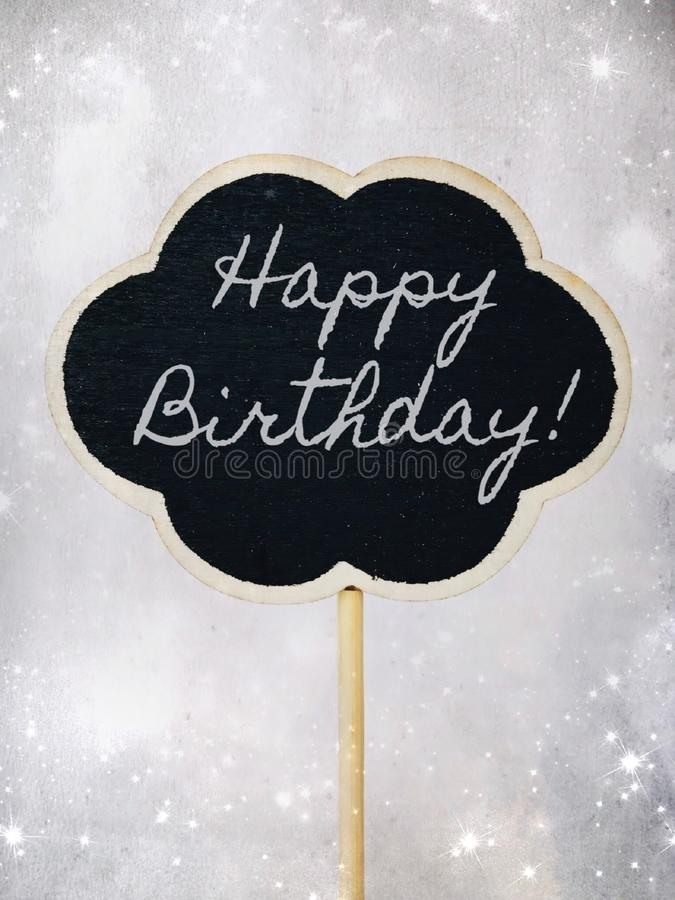 Happy Birthday written in chalk on a small black chalkboard. royalty free stock images