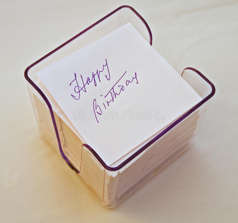 Happy Birthday written on note cube. A note cube with ' Happy Birthday ' written on a memo pad isolated against a bright background stock images