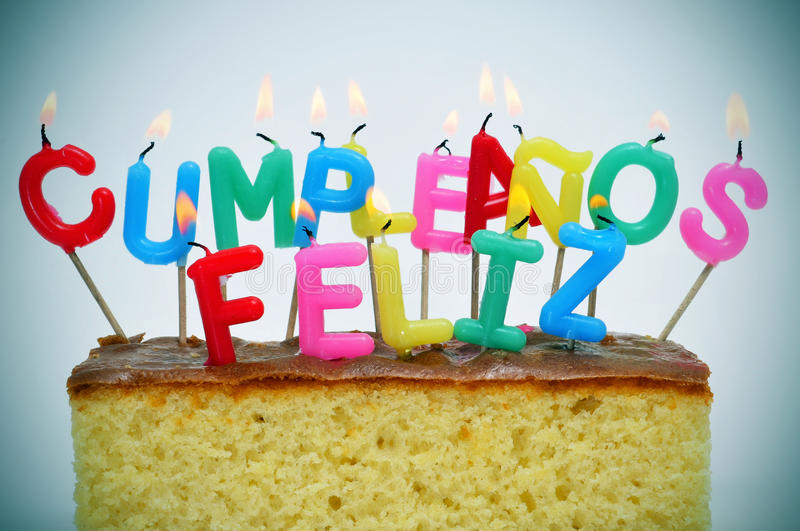 Happy birthday written in spanish. Letter-shaped candles of different colors forming sentence cumpleanos feliz, happy birthday in spanish, on a cake royalty free stock images