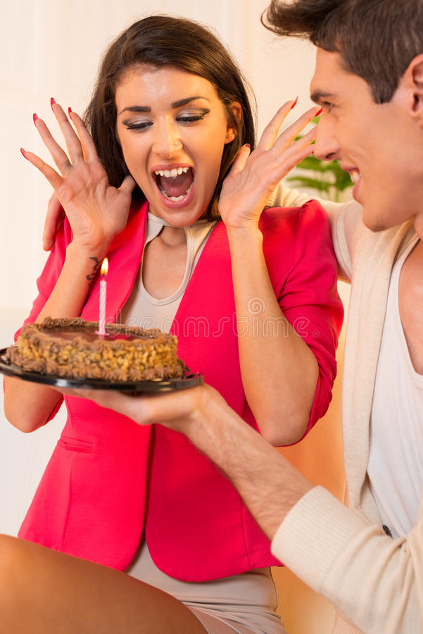Happy Birthday. Young pretty girl with an expression of delight on her face because of the pleasant surprises, birthday cake with a candle, which gives young guy royalty free stock images