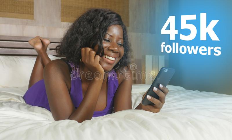 Happy black African American woman lying relaxed on bed using internet mobile phone smiling cheerful networking getting social stock image