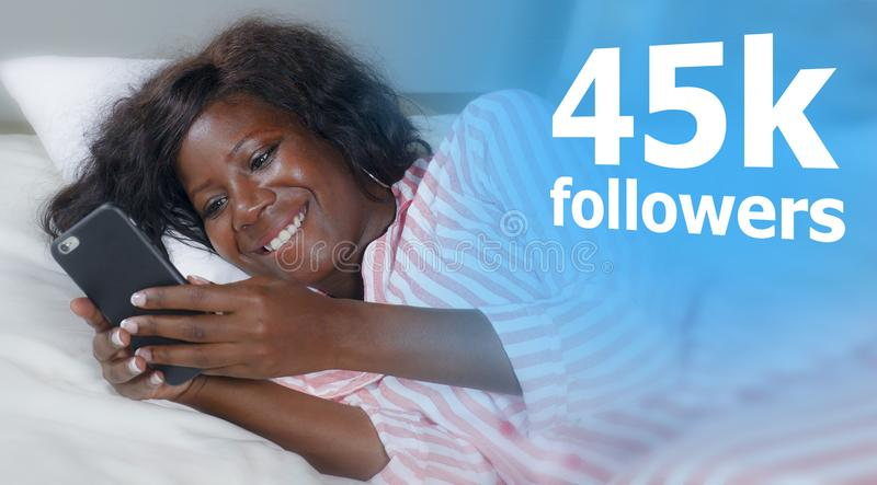 Happy black African American woman lying relaxed on bed using internet mobile phone smiling cheerful networking getting social stock photo