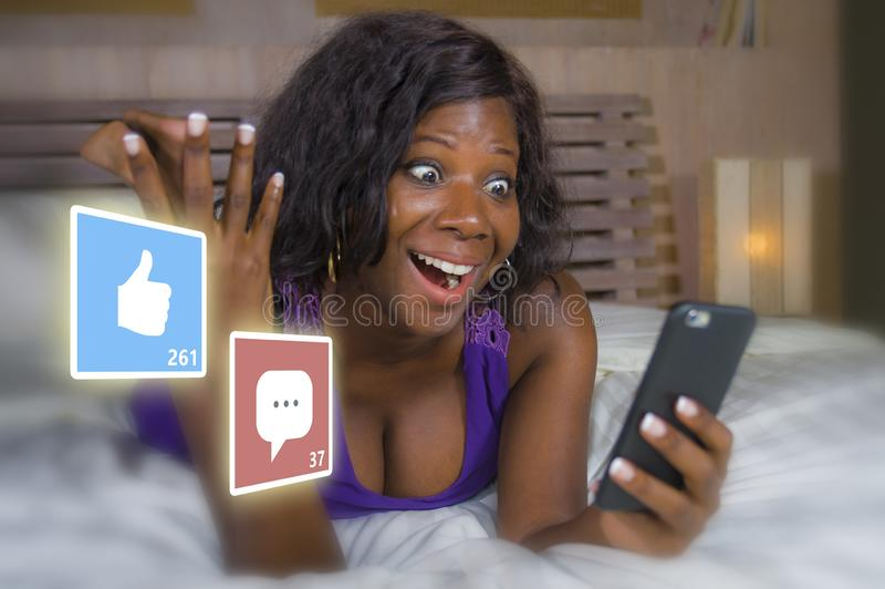 Happy black African American woman in pajamas using mobile phone social media smiling cheerful lying on bed at home receiving royalty free stock photography