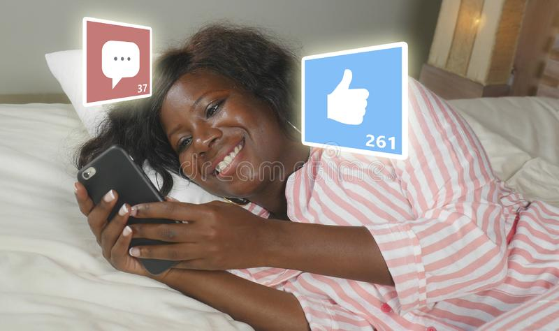 Happy black African American woman in pajamas using mobile phone social media smiling cheerful lying on bed at home receiving stock photography