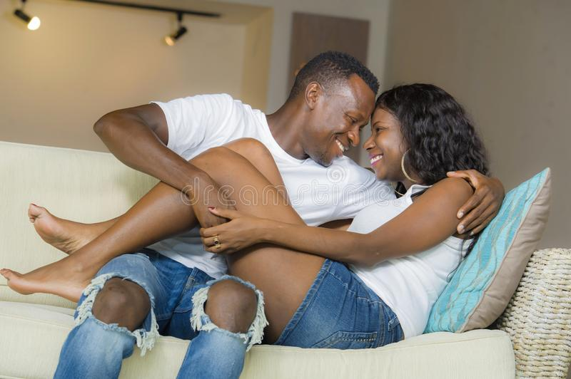 Happy black afro American couple cuddling at home living room sofa couch smiling cheerful having fun relaxed and cozy in. Young beautiful and happy black afro stock photo