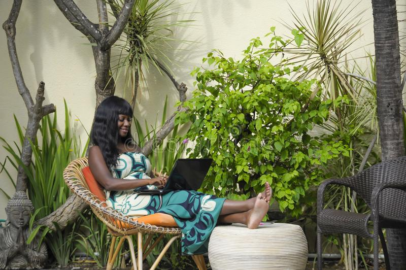 Happy black afro american woman in elegant dress working on luxury terrace villa with laptop excited and happy. Young attractive and happy black afro american stock photo