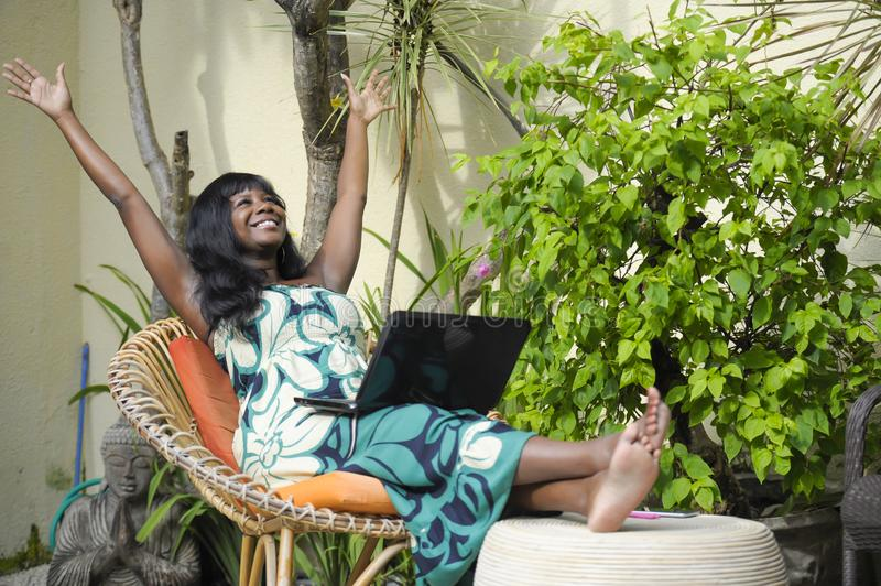 Happy black afro american woman in elegant dress working on luxury terrace villa with laptop excited and happy. Young attractive and happy black afro american royalty free stock images