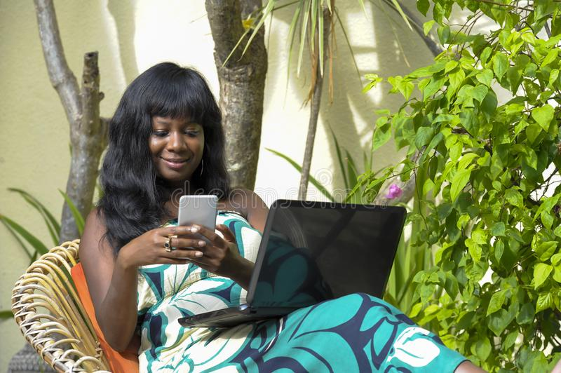 Happy black afro american woman in elegant dress working on luxury terrace villa with laptop and mobile phone. Young attractive and happy black afro american stock images
