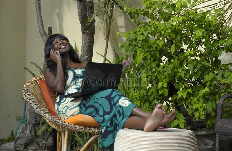 Happy black afro american woman in elegant dress working on luxury terrace villa with laptop talking on mobile phone. Young attractive and happy black afro royalty free stock photography