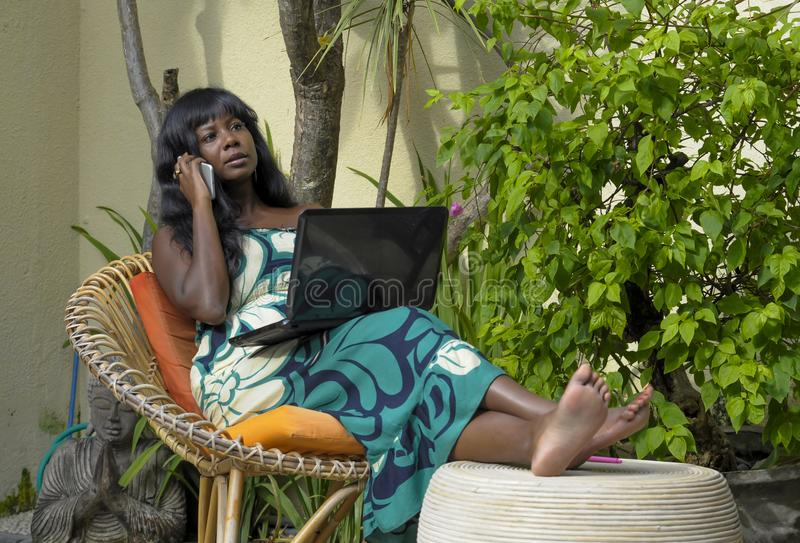 Happy black afro american woman in elegant dress working on luxury terrace villa with laptop talking on mobile phone. Young attractive and happy black afro royalty free stock photo