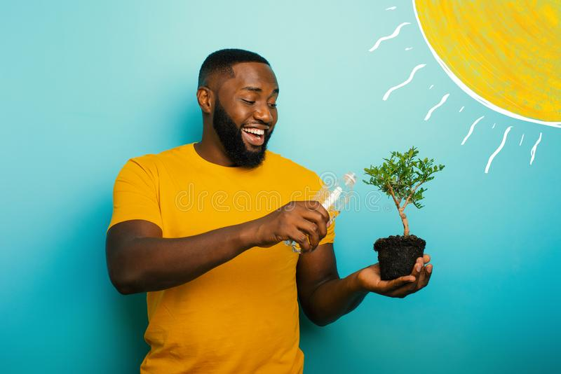 Happy boy watering a small tree ready to be planted. Concept of forestation. Happy black boy watering a small tree ready to be planted. Concept of forestation stock photos
