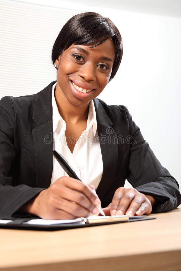 Happy black business woman signing document. Happy young black woman working in office sitting to her desk signing a document. She is looking down to the camera stock photo