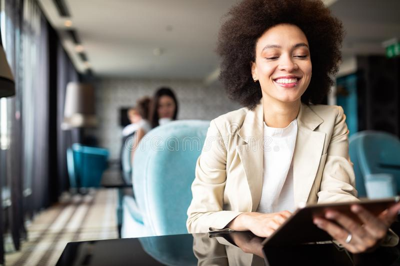 Happy black businesswoman using tablet computer in coffee shop stock photo