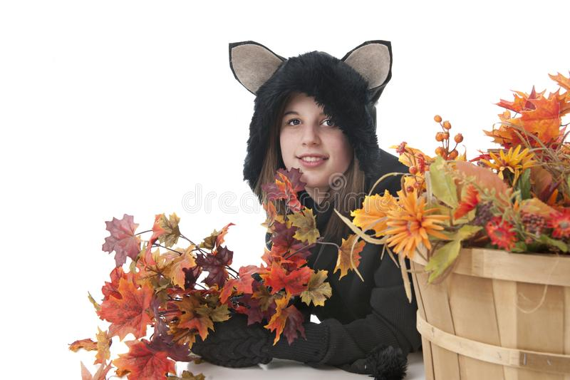 Happy Black Cat among Fall Foliage. An attractive teen girl in a black cat costume, laying beside a basket full of colorful fall foliage. On a white background stock photography