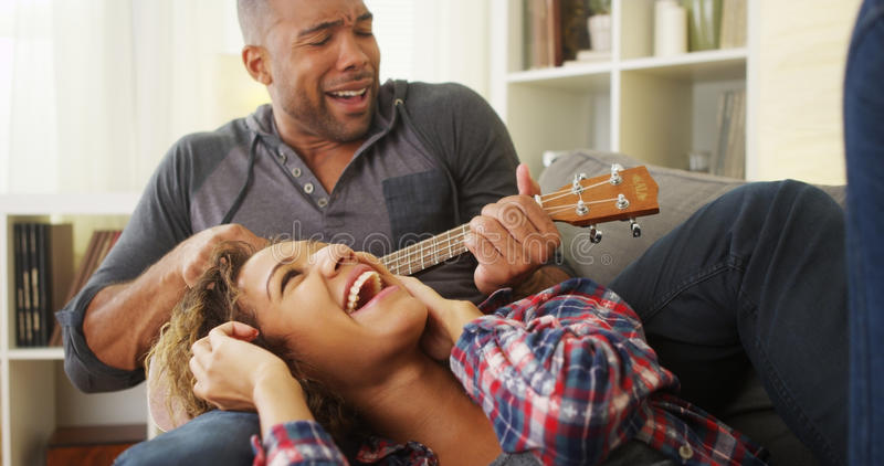 Happy black couple lying on couch with ukulele. At home royalty free stock photography