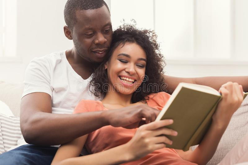Happy black couple reading together at home royalty free stock photo