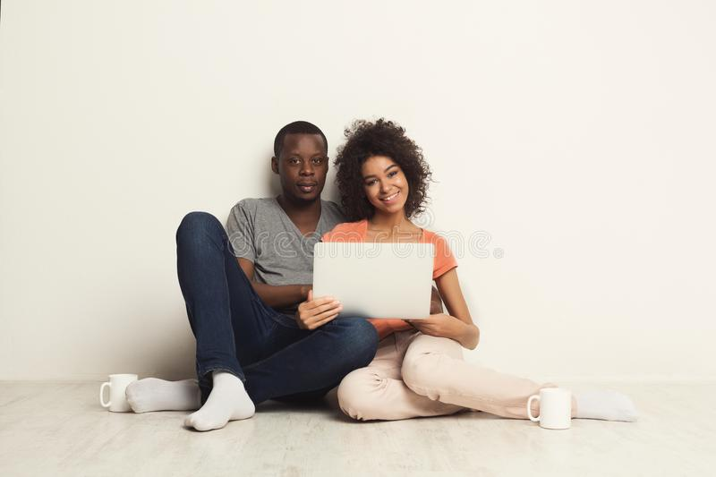 Happy african-american couple shopping online stock photo
