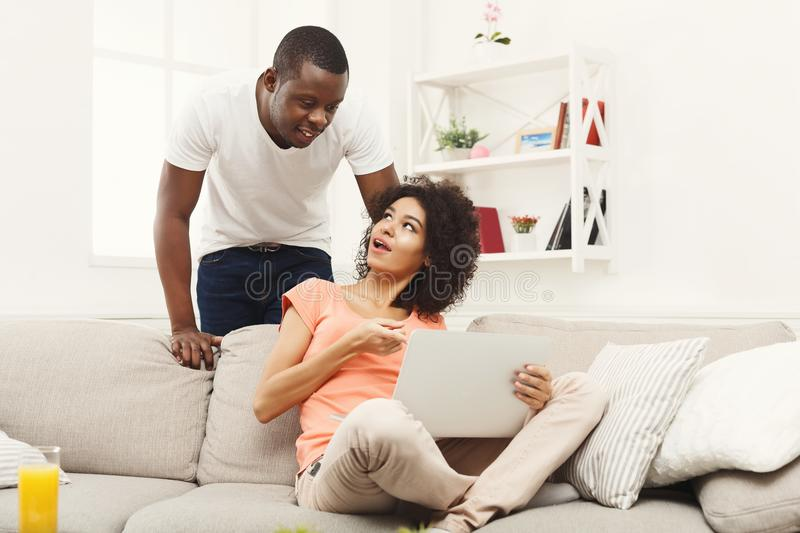 Young african-american couple working on laptop, copy space. Happy black couple working together on laptop sitting on sofa at home. Freelance and remote work royalty free stock photos