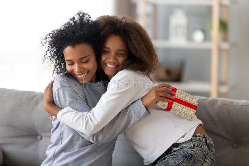 Happy black daughter congratulate young mom presenting gift. Excited African American mother and daughter hugging on couch at home, smiling black teenage girl royalty free stock photo