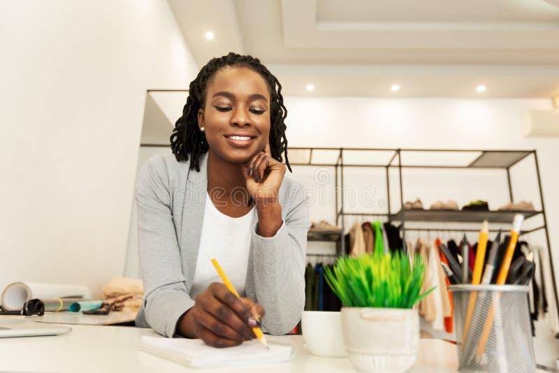 Happy Black Dressmaker Disegna Schizzi In Atelier Di Abbigliamento immagini stock