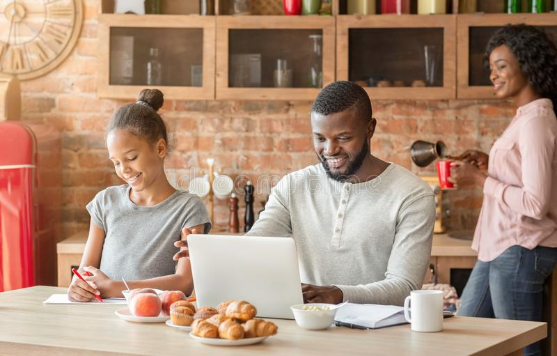 Happy black family having breakfast together in kitchen royalty free stock image