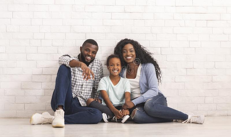 Happy Black Family With Little Daughter Sitting On Floor Together stock image