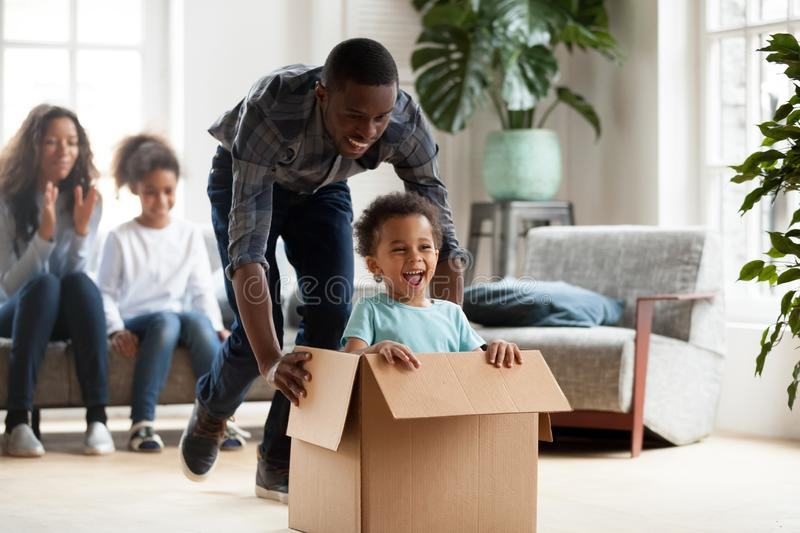 Happy black family play with kids moving to new home royalty free stock photos