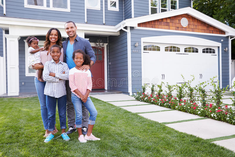 Happy black family standing outside their house stock image