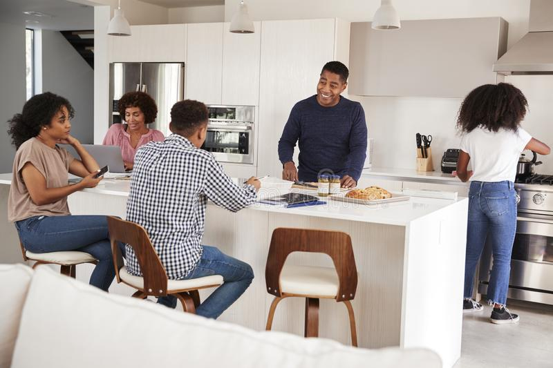 Happy African American  family talking and preparing a family meal together in their kitchen royalty free stock photography