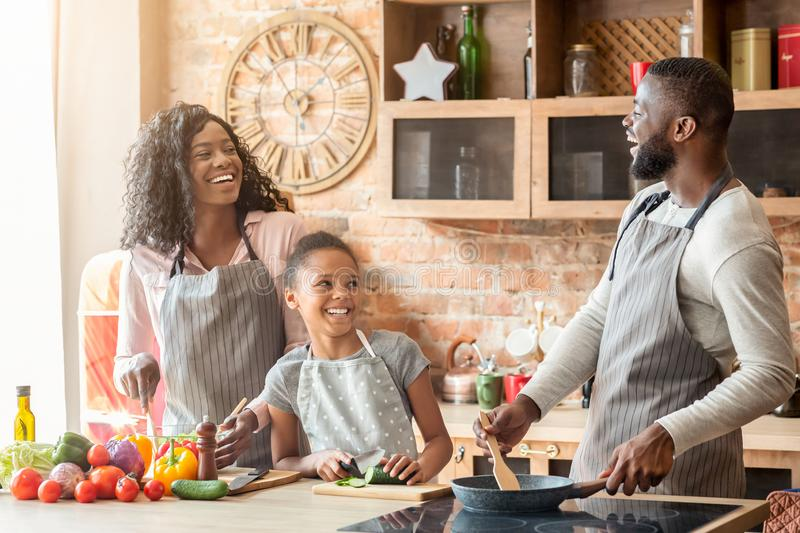 Happy black family of three laughing at kitchen stock photos