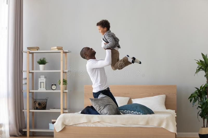 Happy black father holding lifting child son playing on bed. Happy family loving black father holding lifting cute small mixed race child son playing on bed stock photo