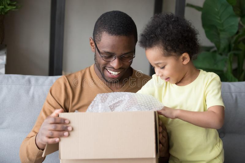 Happy black father and little kid son open cardboard box. Happy black father and little kid son opening cardboard box looking inside, african american dad with stock image