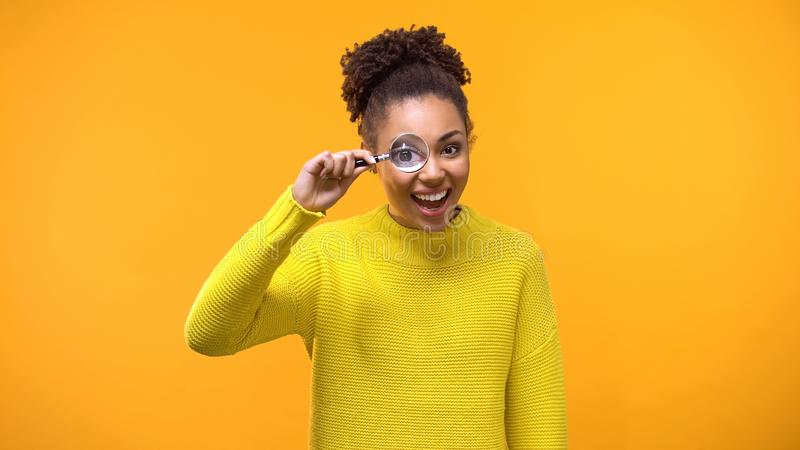 Happy black female looking camera through magnifying lens, shocking news, search stock images
