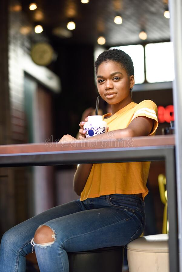 Smiling black woman with very short hair drinking a cocktail in an urban cafe. Happy black girl with very short hair drinking a cocktail in an urban cafe royalty free stock image