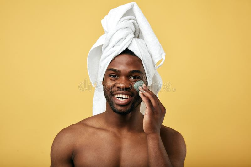 Happy black good looking guy massaging his face. And putting cream on it, isolated over yellow background stock photos