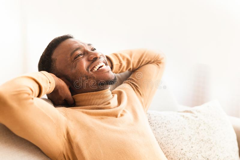 Happy Black Guy Relaxing Sitting On Couch At Home royalty free stock images