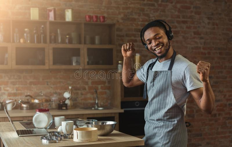 Happy black man listening to music and dancing in kitchen stock photos