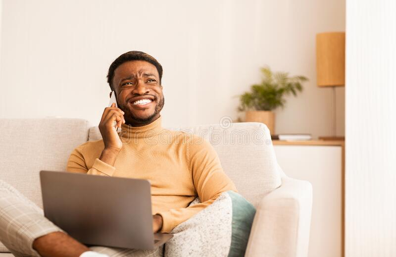 Happy Black Man Talking On Cellphone Working On Laptop Indoor stock photography