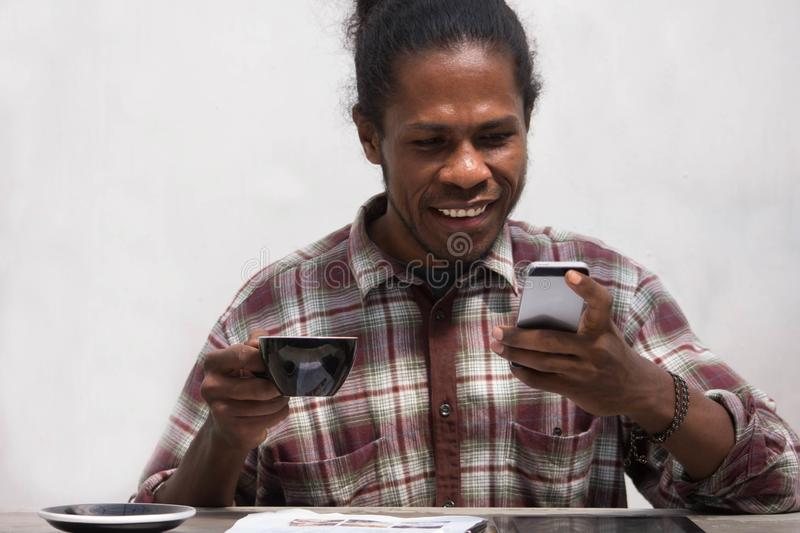 A Happy black man using smart phone at home. Smiling young african man at home sitting on couch reading phone message. young papua royalty free stock photography