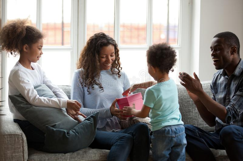 Happy black mom receiving gift box with present from son. Happy black mom receiving gift box with present from mixed race kid son and family celebrating birthday stock photography
