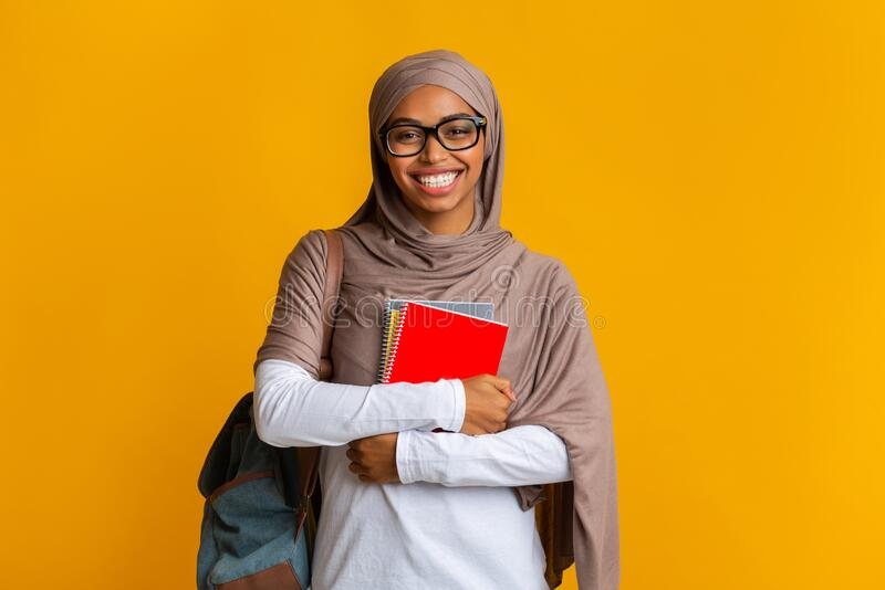 Happy black muslim student girl in hijab with backpack and notepads stock photo