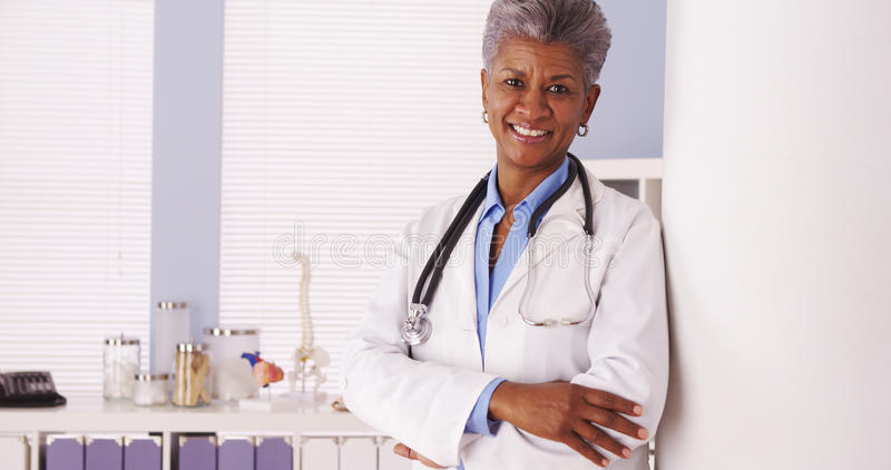 Happy Black Senior doctor smiling at camera. Black Senior doctor standing in office royalty free stock photography
