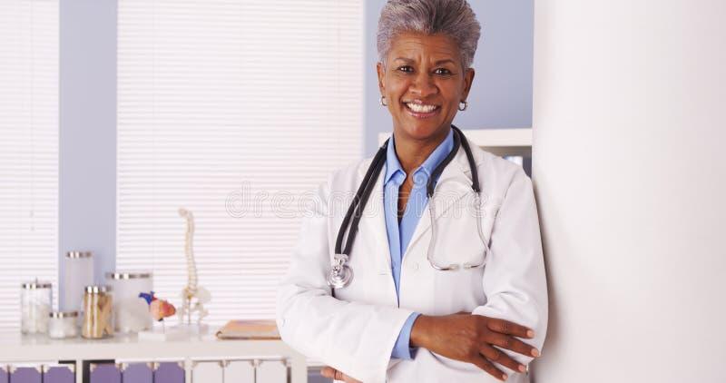Happy Black Senior doctor smiling at camera. Black Senior doctor standing in office stock photo