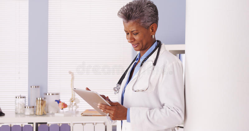 Happy Black Senior doctor standing in office with tablet stock photo